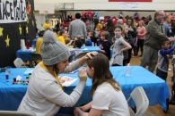 An Augustana student paints the face of a child during the annual Rocky Road event in the Augustana gymnasium Jan. 27.