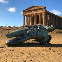 The Temple of Concordia in the Valley of the Temples in Sicily with a modern statue of Icarus in front.