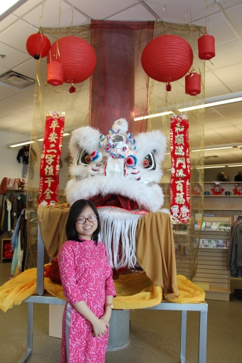 Hien Nguyen stands in front of a Chinese dragon's head in the Augustana Bookstore.